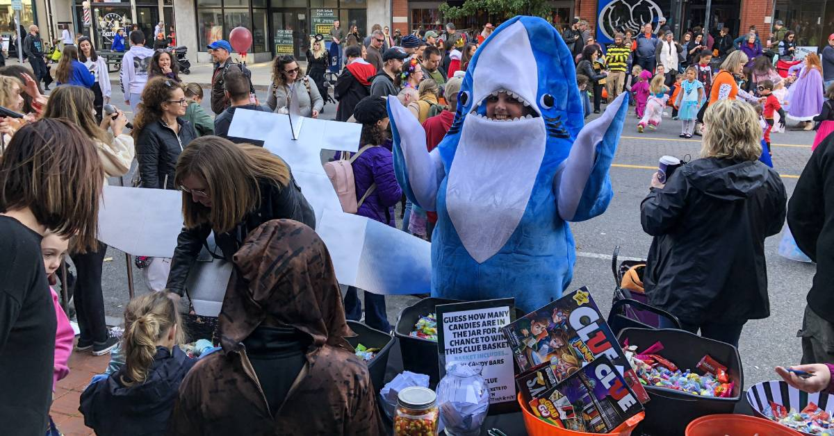 Kids in costume collect candy from person dressed as a shark