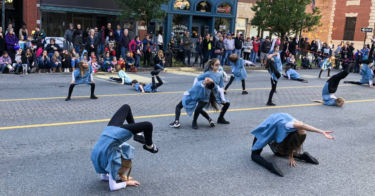 Young dancers in hospital gowns perform on closed off street