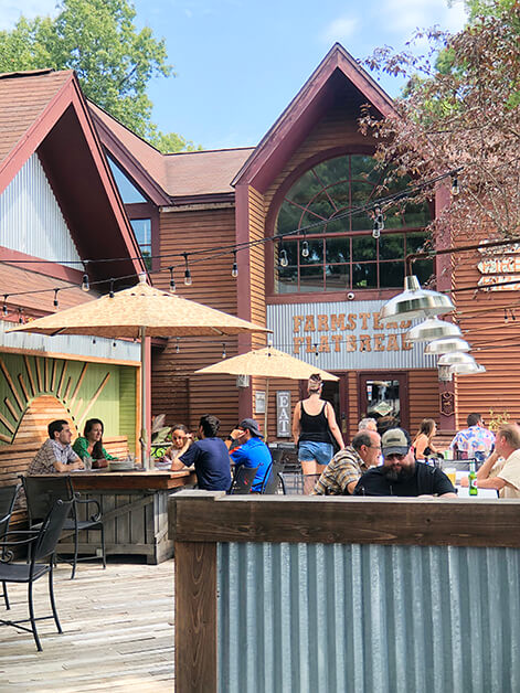 People sit on a patio outside of a large brown building that has a Farmstead Flatbread sign at the front entrance.