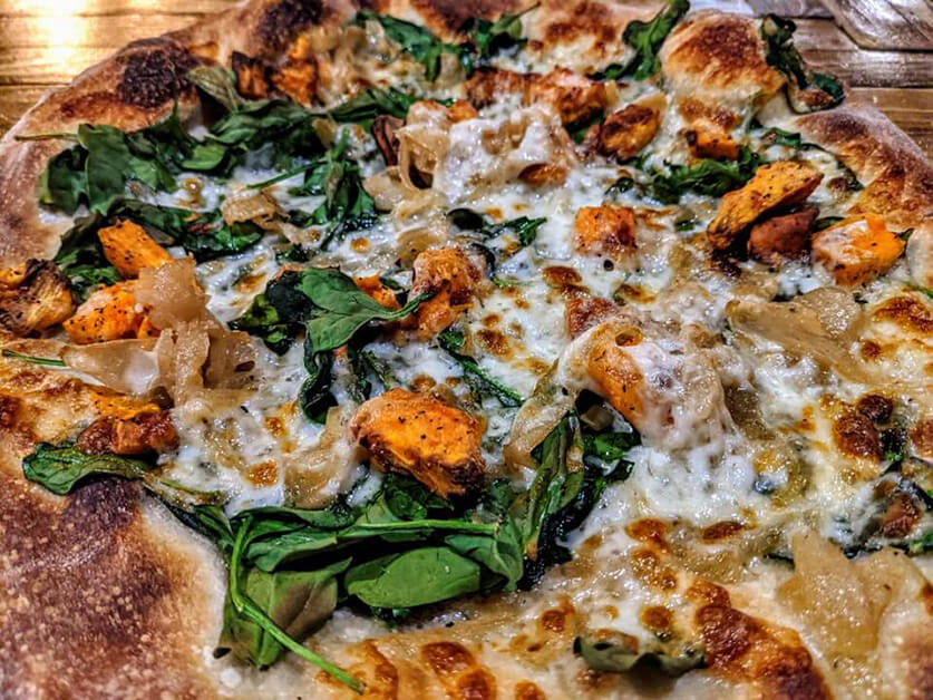 A pizza with sweet potato, cheese, and spinach