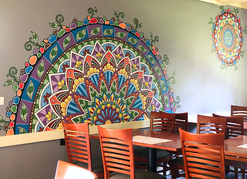 A brightly colored mural is seen on the wall, and a table and chairs.