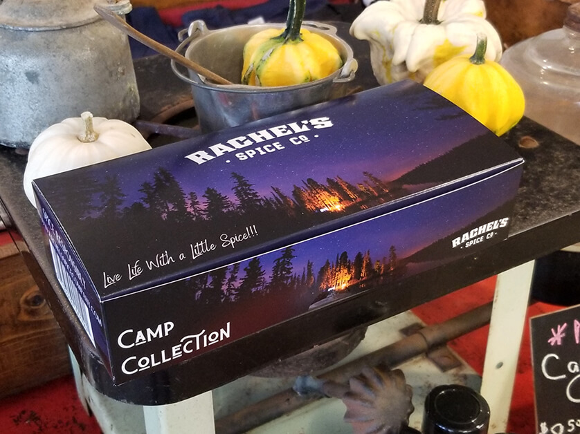 A blue box with a campfire photo that says Camp Collection on it, and includes Rachel's Spice Company logo