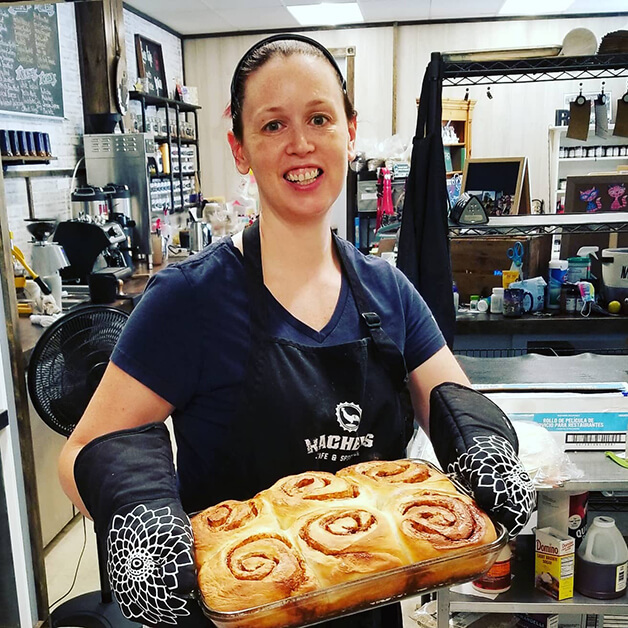 A smiling woman holds a tray of six giant cinnamon rolls.
