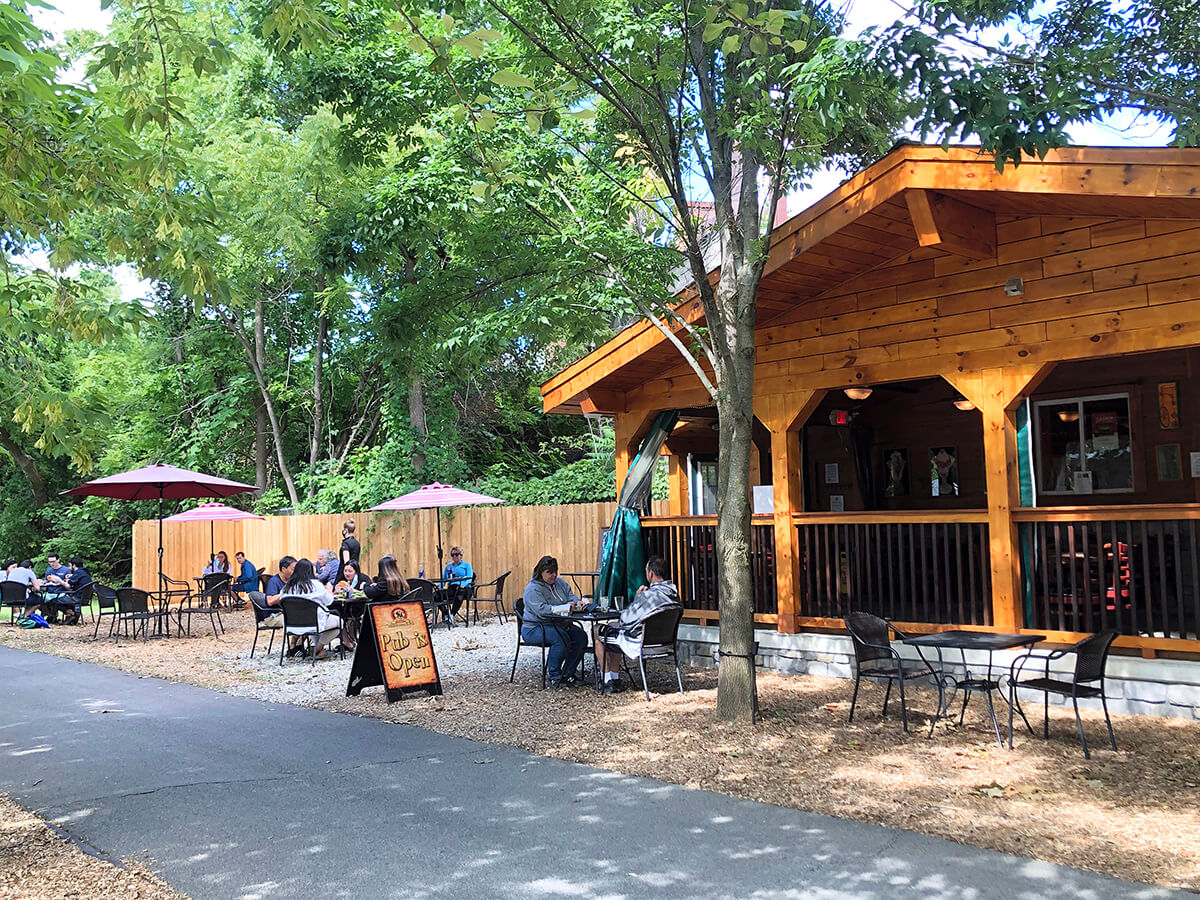 An outside view of Cooper's Cave dining deck along trees and a bikeway path.