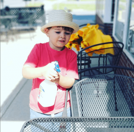 A small boy in a red shirt, wearing a hat, uses a spray bottle to clean an outdoor table.