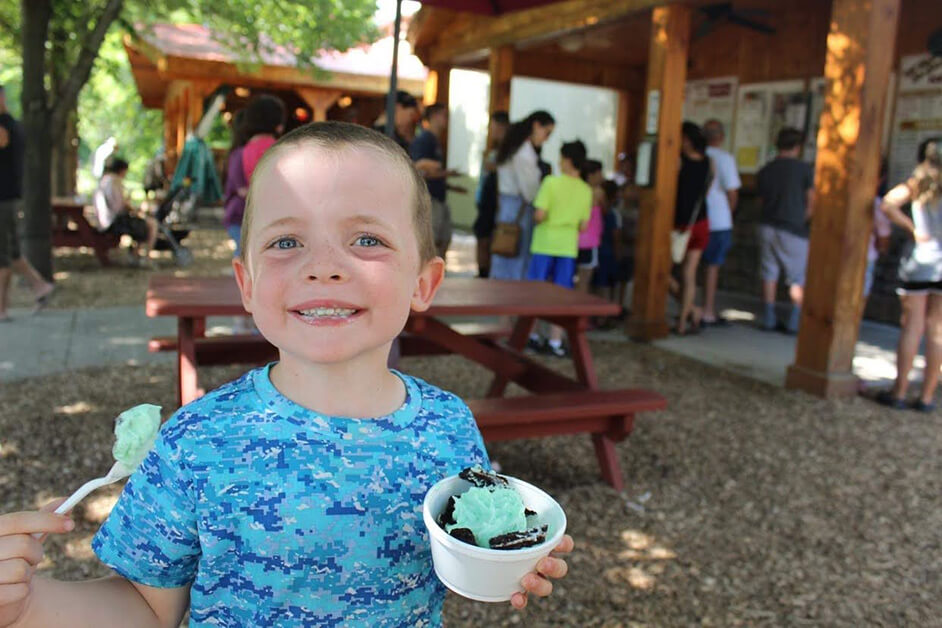 A smiling boy holds a dish of mint ice cream in front of a picnic table and a line of people ordering ice cream.