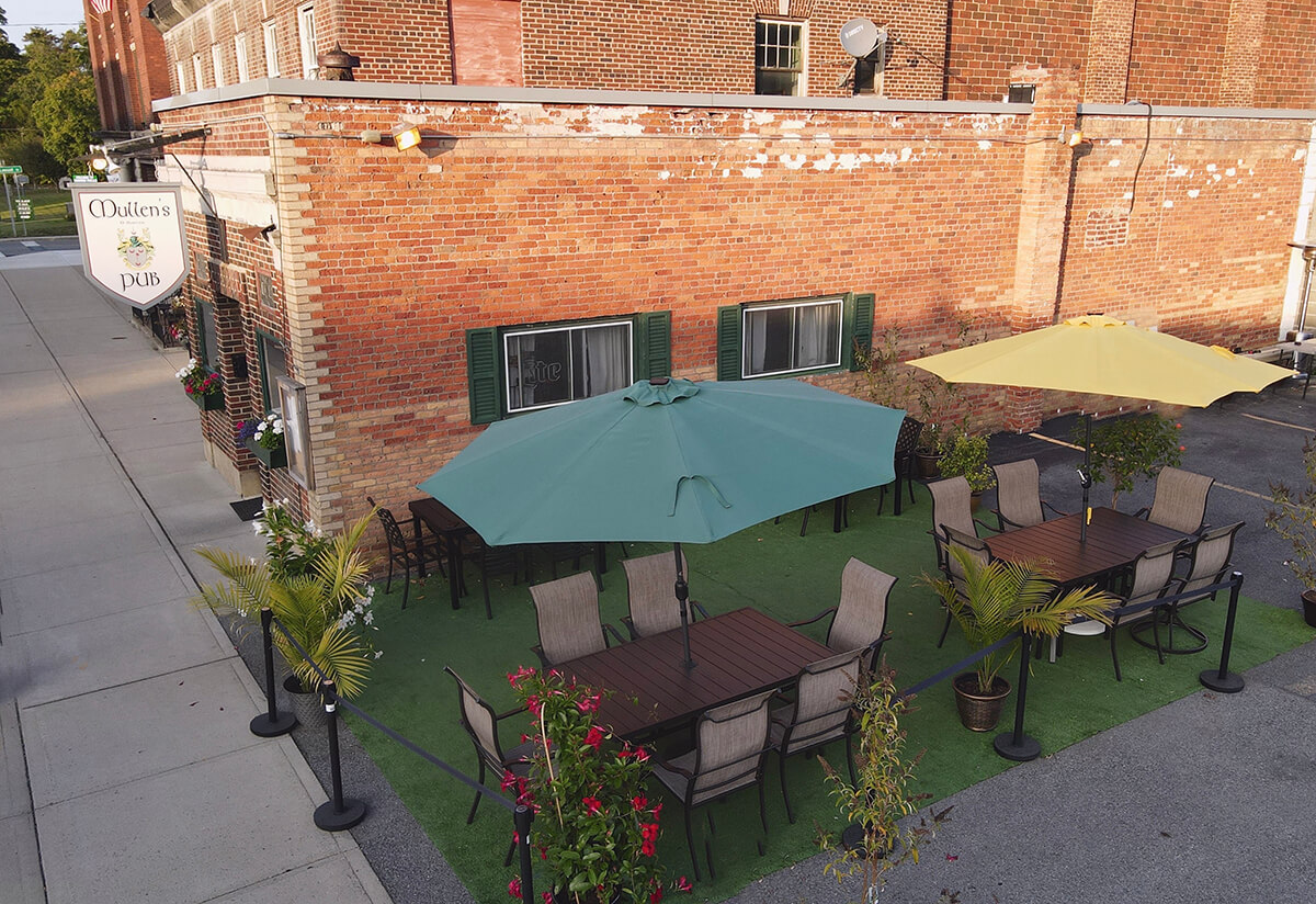 A brick building with a Mullens Pub sign is in the background. A green floor with plants and outdoor tables with umbrellas sits in the foreground.