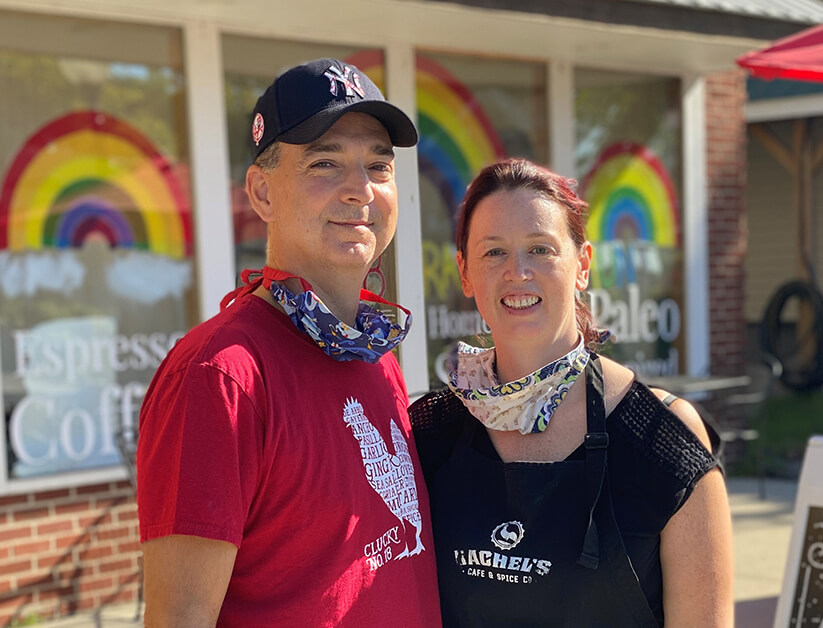 A man in a red shirt and a New York Yankees baseball cap smiles at the camera next to a woman, also smiling, wearing a Rachel's Cafe and Spice Company black t-shirt. Both have masks around their necks, and appear outside with windows in the background decorated with rainbows.