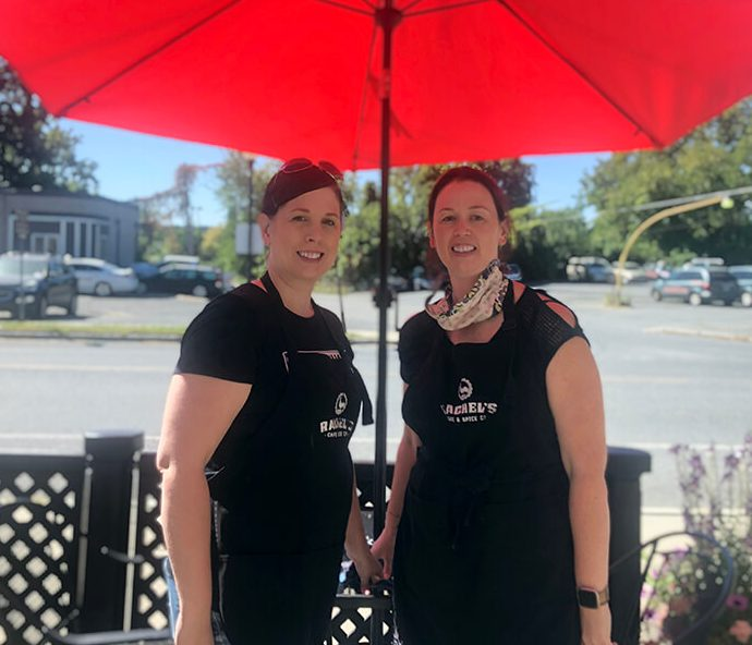 Two women smile under a red umbrella next to an outdoor table