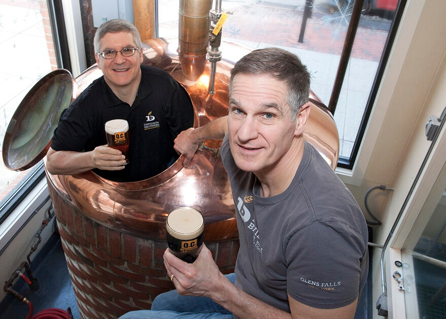 A man wearing a black shirt holds a beer while standing in a copper beer kettle. Another man holding a beer leans against the kettle and wears a gray Davidson Brothers shirt.