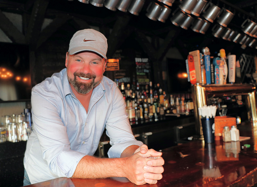 A man wearing a gray hat smiles and leans on a bar.