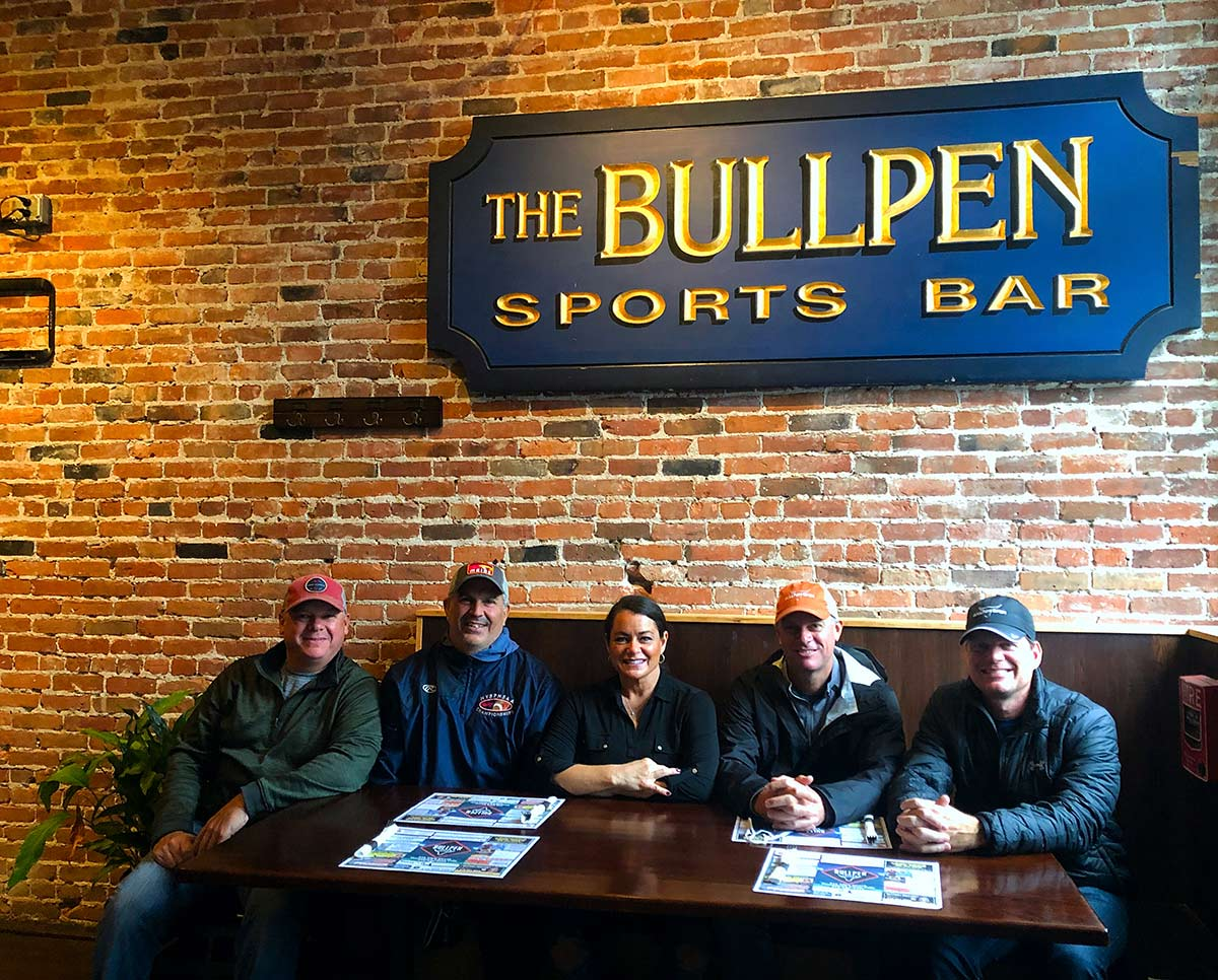 """Two men, a woman, and two additional men sit in a restaurant booth against a brick wall with a sign that says """"The Bullpen Sports Bar."""""""