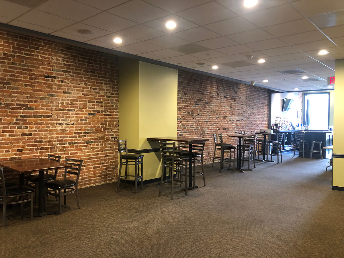 A large room with three high top tables and brick and green walls.