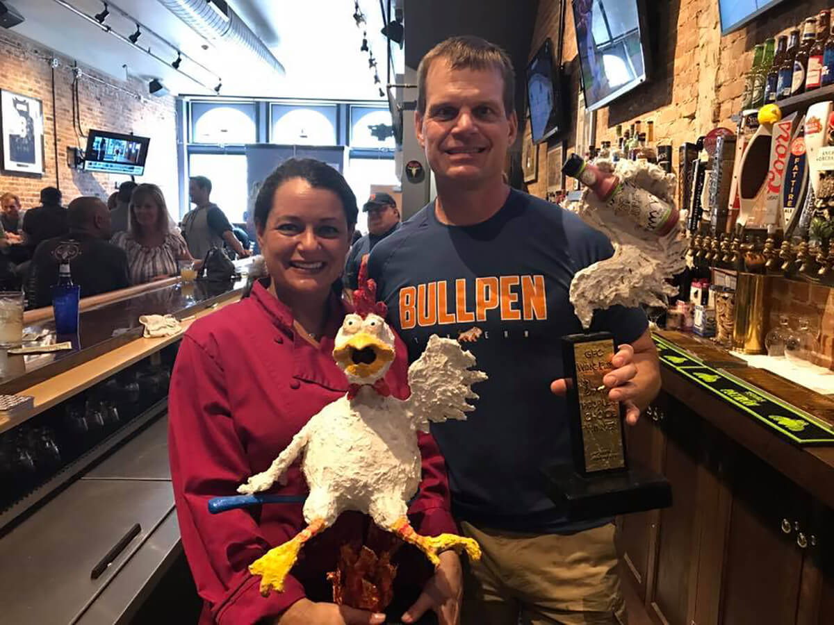 A woman holds a chicken sculpture while standing next to a man in a Bullpen t-shirt, holding a trophy with what appears to be hot sauce.