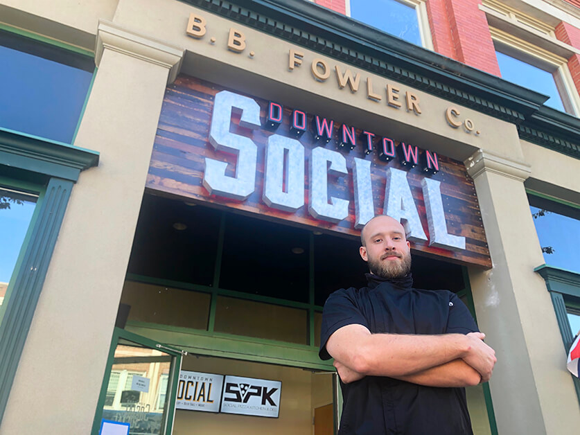 """A man in black stands in front of a building that says """"B.B. Fowler Co."""" and has a """"Downtown Social"""" sign"""