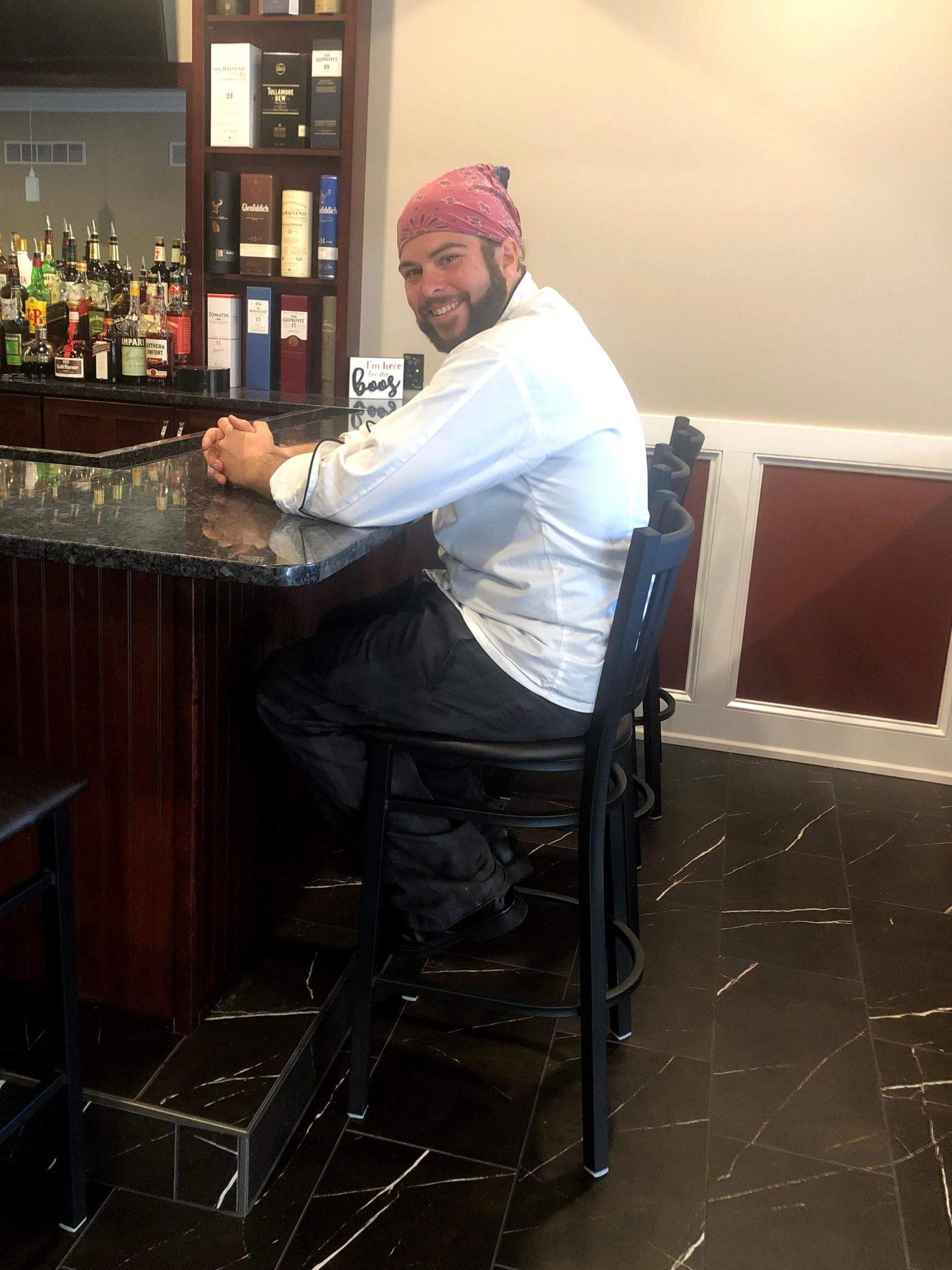 A man wearing a head bandana sits at a bar.