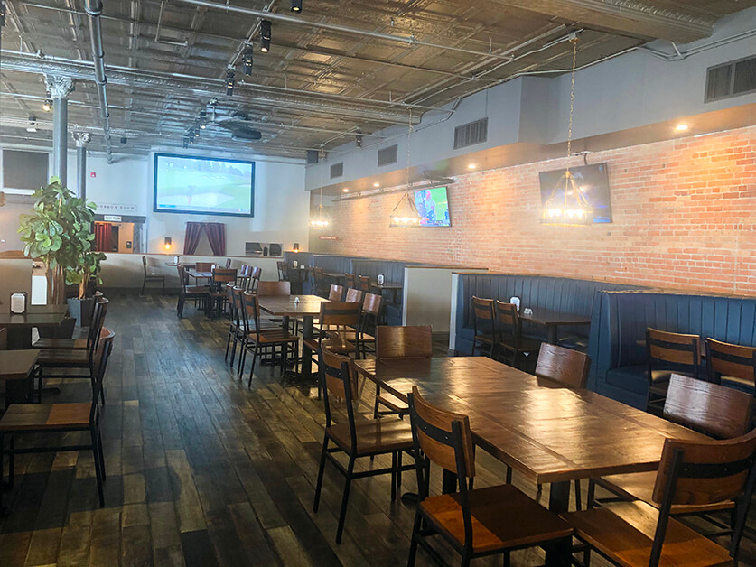 A large room with tables and booths plus video screens on a brick wall