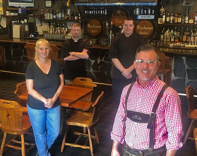 A woman with a long, blonde ponytail stands at front left in front of a table and wears a back shirt and jeans. Two men in black stand in the background in front of a bar. A man wearing glasses and lederhosen stands in the foreground at front right.