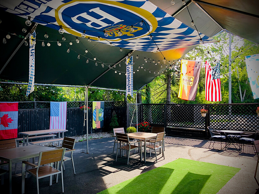Two outdoor tables are pictures under a canopy with flags in a biergarten