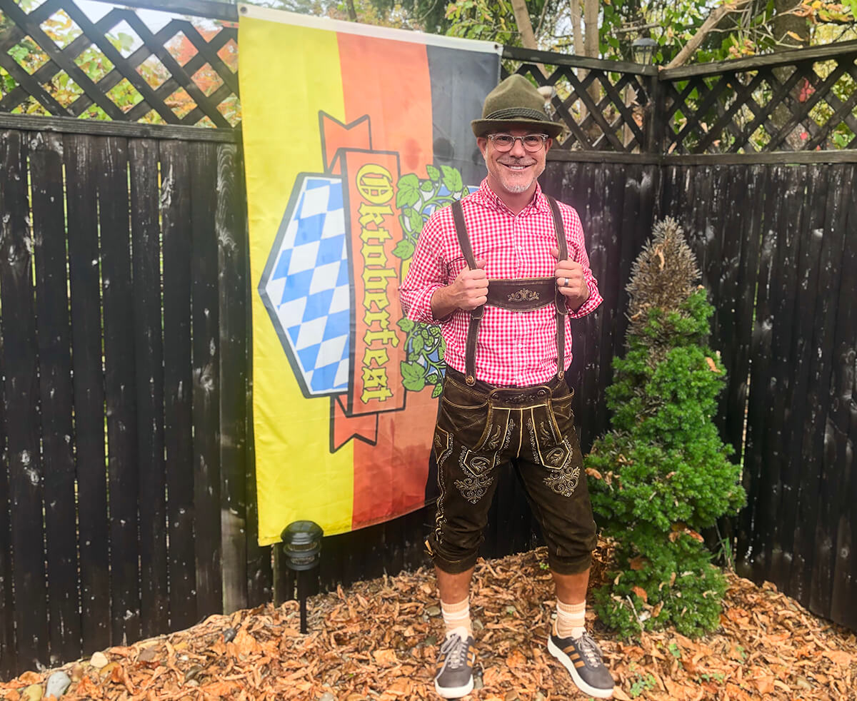 A man wearing glasses and a hat holds the suspenders of his lederhosen. An Oktoberfest flag is in the background and he stands next to a small tree.