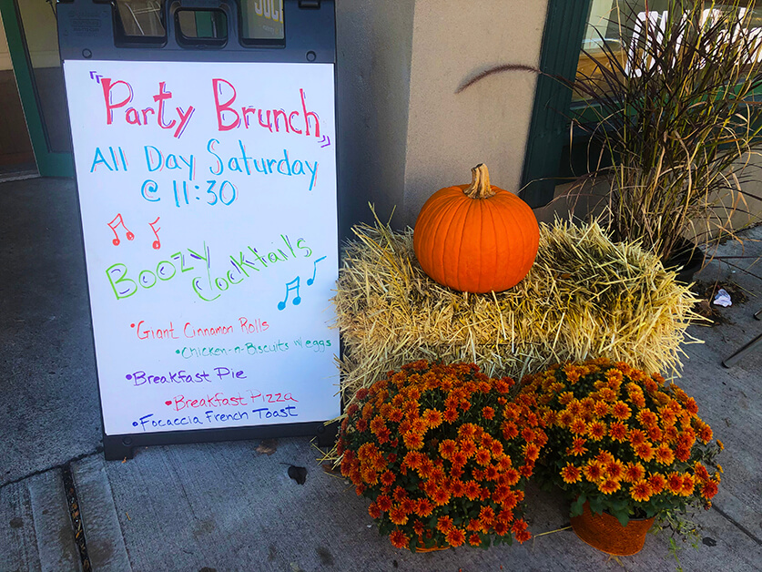 A sandwich board advertising Party Brunch aside a haystack, pumpkin, and two pots of orange mums