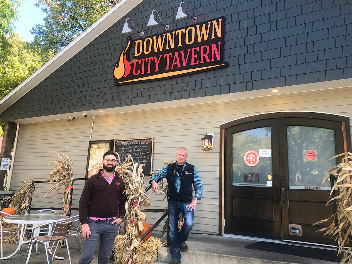 Two men stand in front of a cream building with a blue roof and a Downtown City Tavern sign.