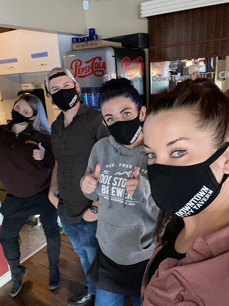 "A woman, man, and two women wear black face masks that say ""Downtown City Tavern."""