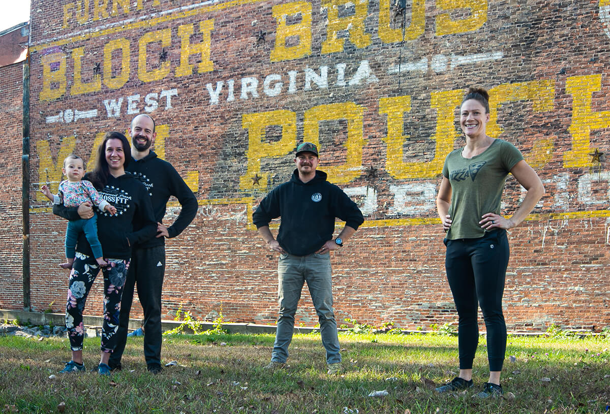 Standing in front of a brick wall with vintage font, a man and woman holding a baby stand to the left wearing Undewood Park Crossfit sweatshirts. A man wearing a black Slick Fin Brewing Company sweatshirt is in the middle. A woman wearing a Stumpy's Pizzeria shirt is on the right.