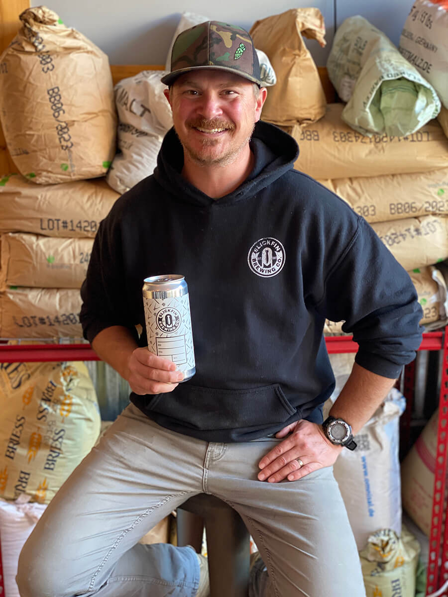 A man sits with bags of grain in the backgroudn. He is swearing a black hooded sweatshirt that says Slick Fin Brewing Company and a camouflage baseball cap, while holding a beer can.