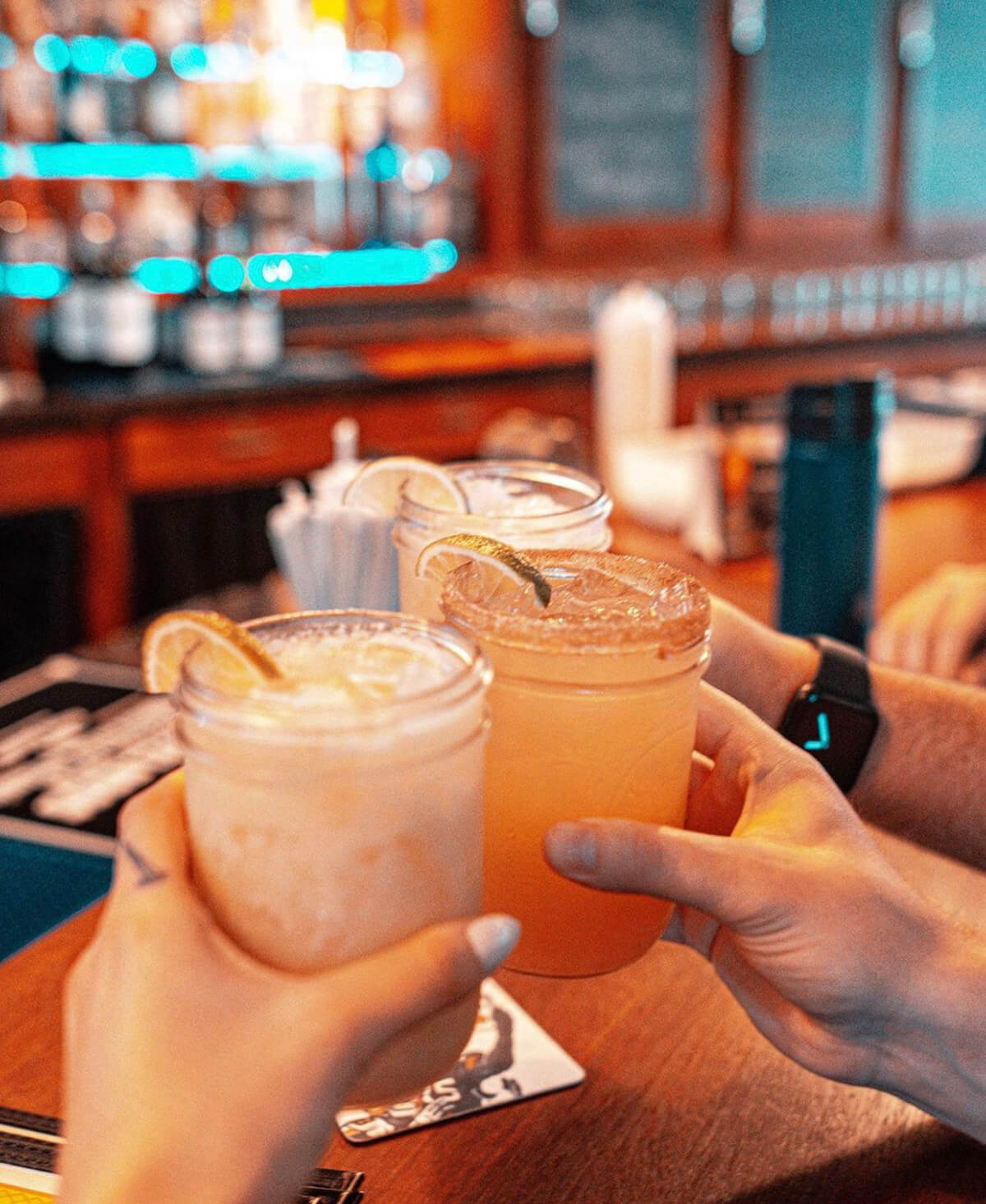 Hands come together with three margaritas in a toast.