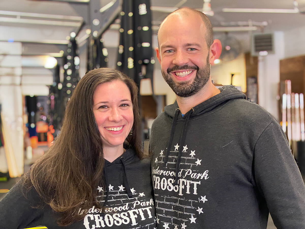A woman with long brown hair stands next to a man with a beard. Both wear Underwood Park CrossFit sweatshirts and gym equipment is in the background.
