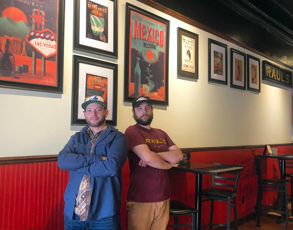 Two men stand back to back with their arms crossed in front of highly decorated red wall.  Both men wear baseball caps.