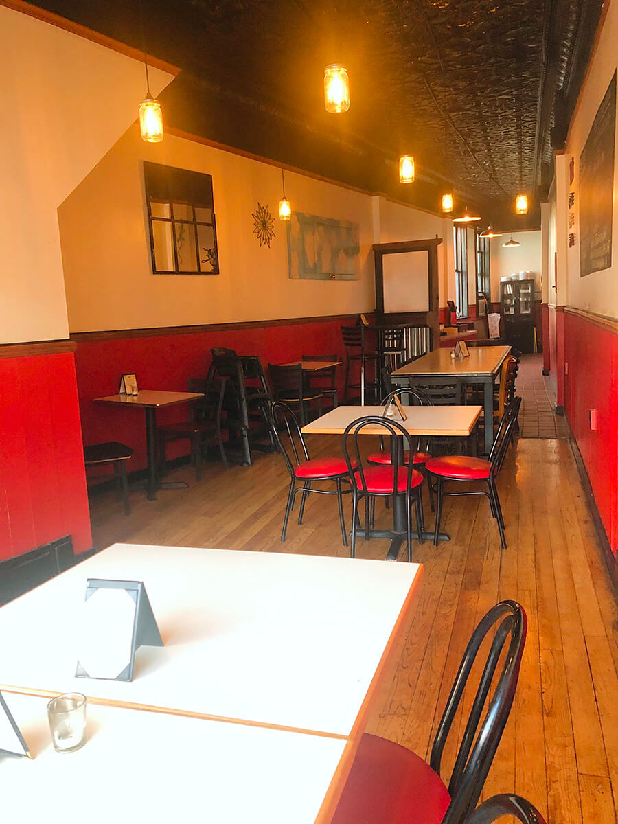 A long, narrow room of dining tables.  The walls are red and the floor is wood.