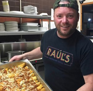 A man wearing a black backwards cap and wearing a black t-shirt that says Raul's carries a large tray.