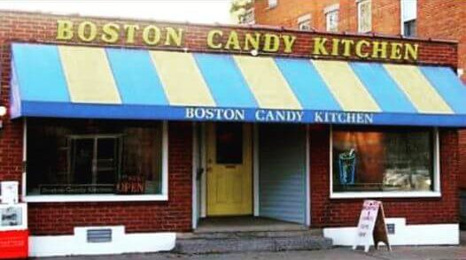 A brick building with a yellow door and a blue and yellow striped roof that says Boston Candy Kitchen along the top of the building.