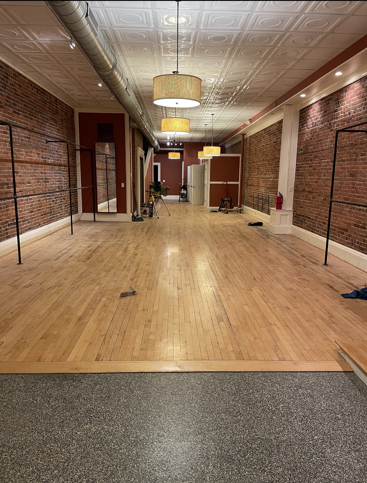 A long room with a wood floor featuring a white tiled ceiling, brick walls on the right, and burgundy painted walls on the left and back sides.
