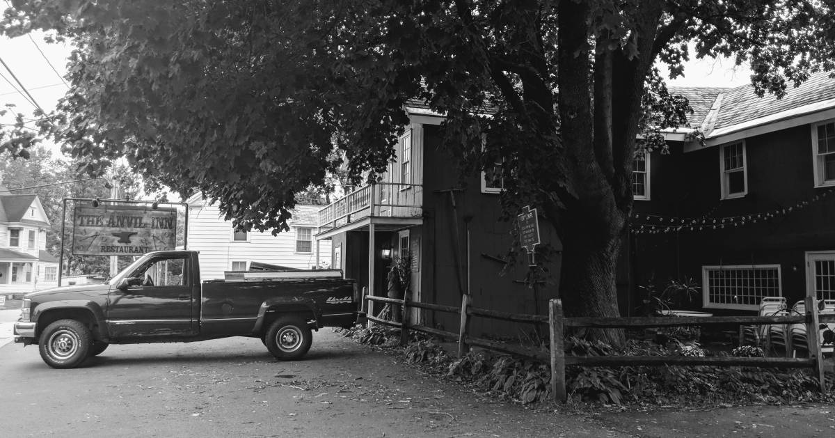 black and white image of restaurant with truck in front