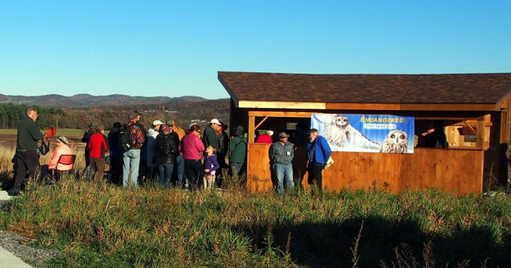 people gathered by a small hut with a Washington County Grasslands IBA poster on it