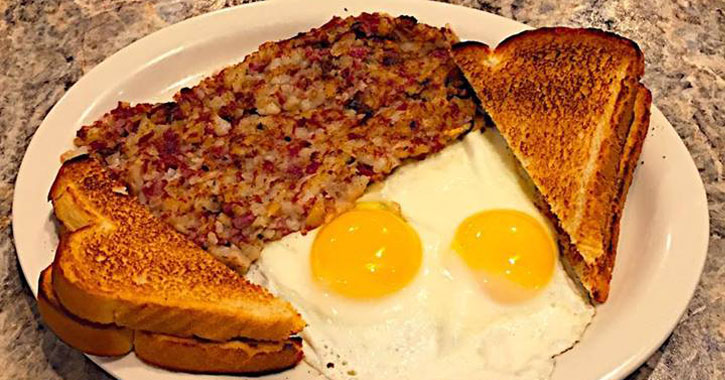 Sunny-side up eggs, toast, and corned beef hash on a white plate