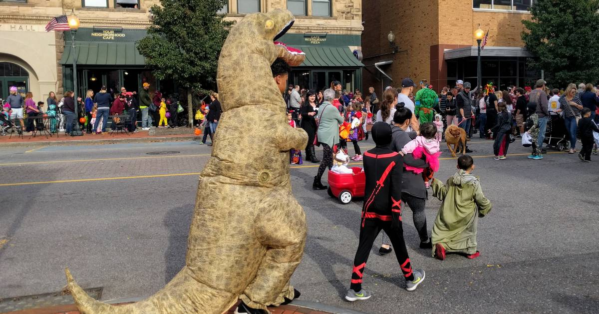 kid in dinosaur costume at Halloween event