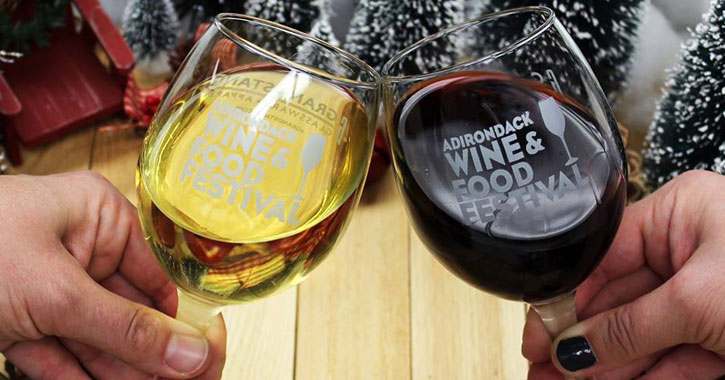 two wine glasses cheersing with a winter background
