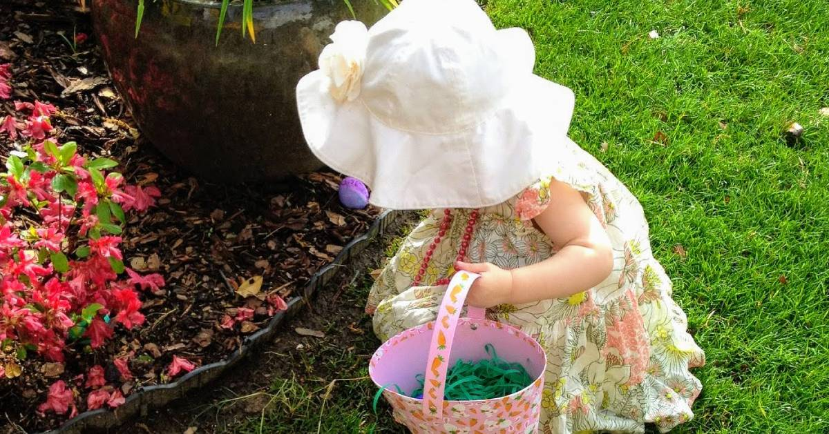 a little girl in a bonnette with a little basket hunting for eggs outside