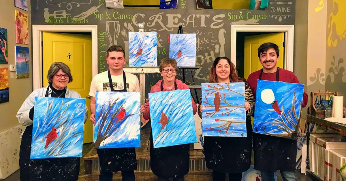five people holding up paint and sip paintings