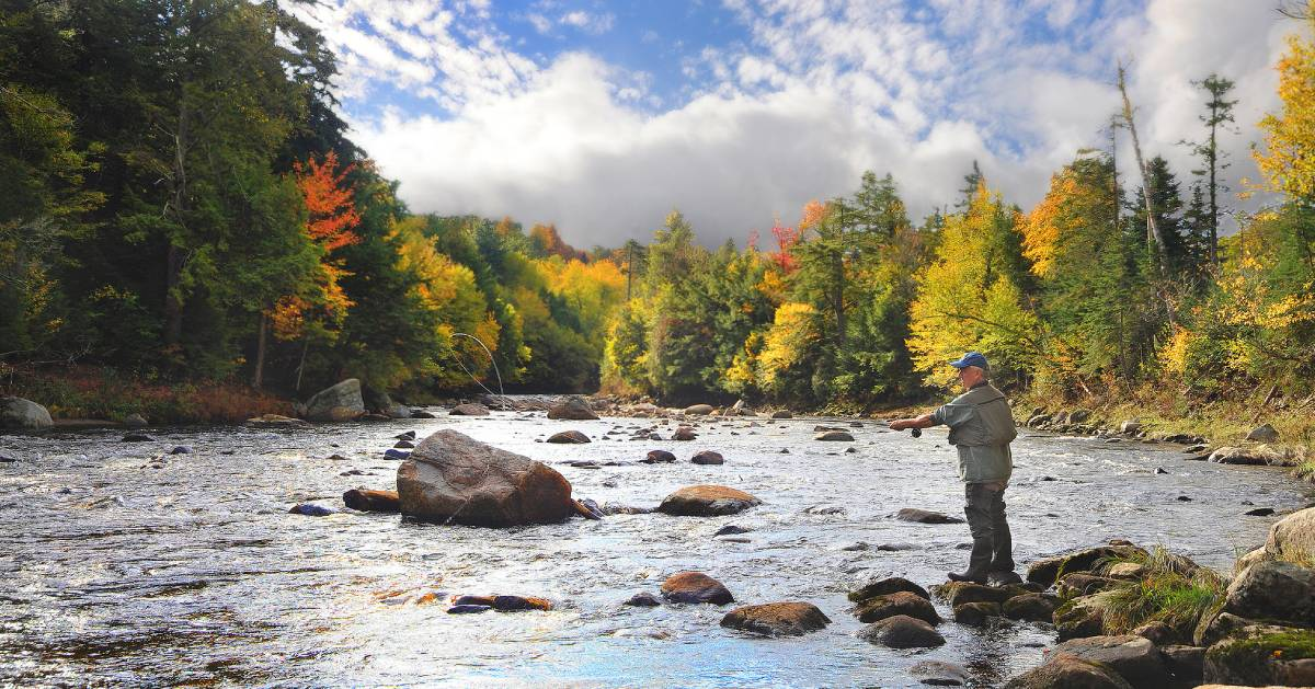 person fishing in Adirondacks during fall