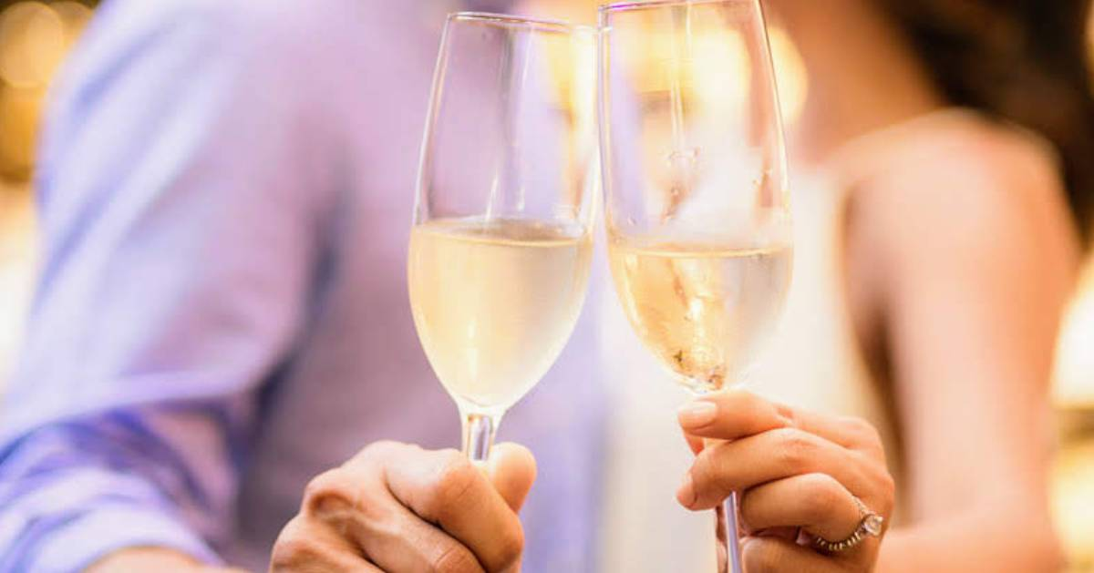 close up of couple cheersing with champagne flutes