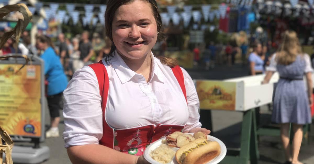girl in German attire holding German food