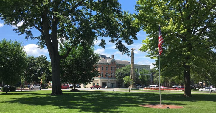 american flag, trees, and monument in downtown glens falls