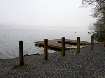 Morning fog over a lake as seen from dock