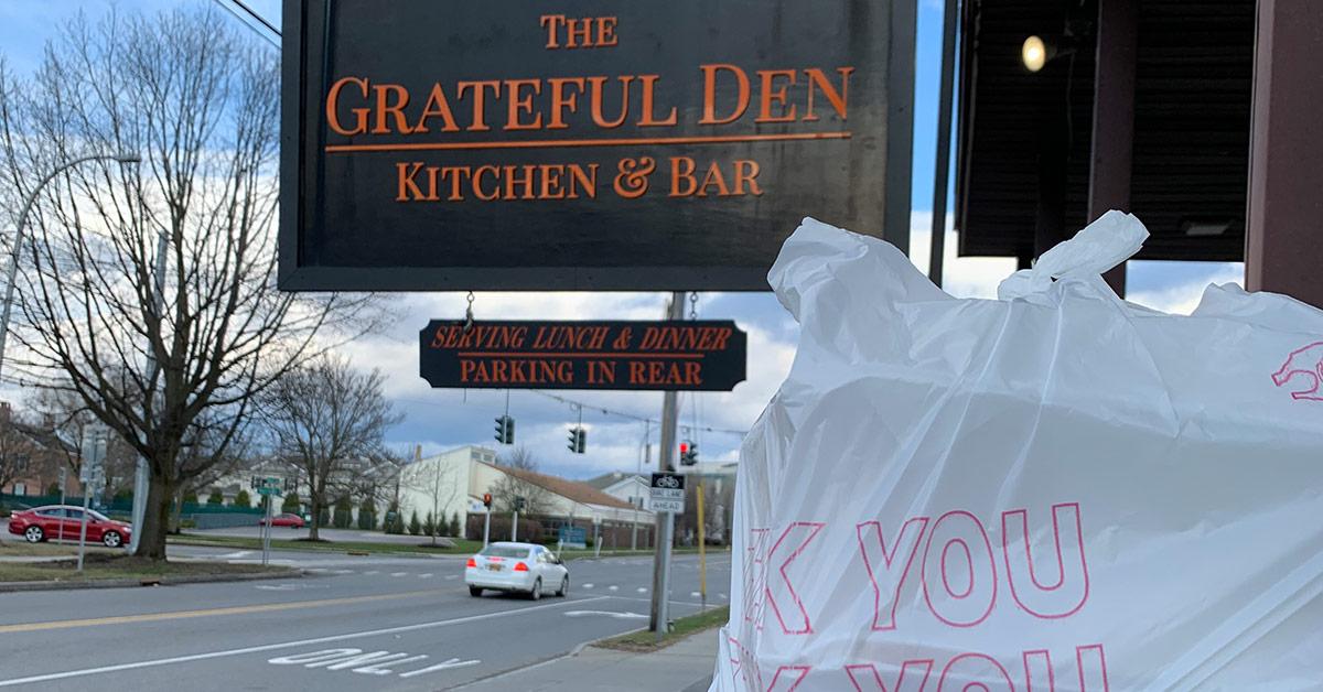 takeout bag in front of grateful den sign