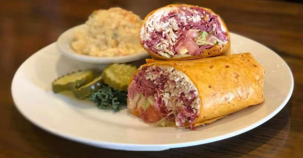 wrap on a plate with potato salad and pickle slices